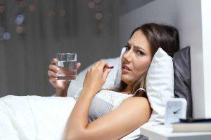 Mujer tomando pastillas para dormir